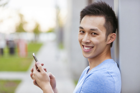 Smiling young asian man holding smart phone and looking at camera on city sidewalk