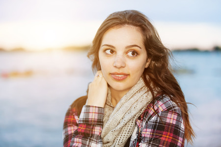 sidelong: Candid portrait of young brunette woman at sunset looking away with copy space Stock Photo