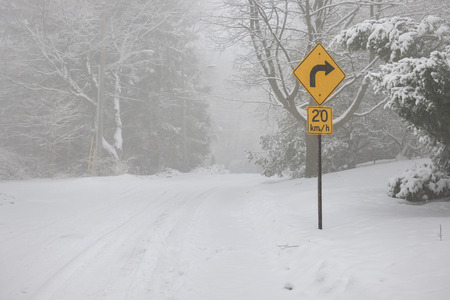 Winter road covered with thick snow and yellow speed limit sign. Toronto, Canada. photo