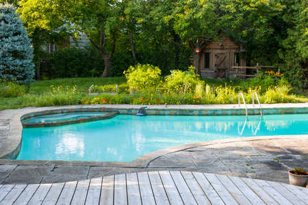 inground: Backyard with outdoor inground residential swimming pool, garden, deck and stone patio Stock Photo