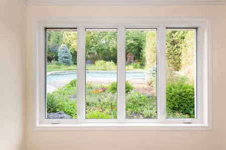 VENTANAS: Gran ventana de cuatro panel mirando en el patio trasero de verano con piscina y jardín