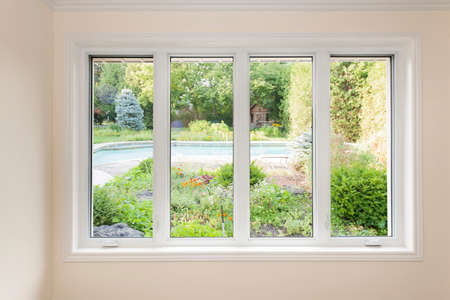 windows: Large four pane window looking on summer backyard with pool and garden Stock Photo