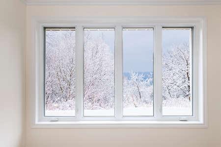 Große vier Fenster Fenster mit Blick auf schneebedeckten Bäume im Winter