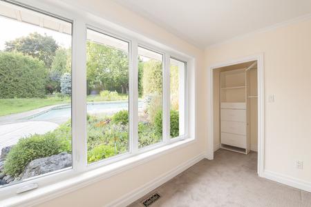 Große Fenster im leeren Schlafzimmer mit Blick auf Sommer Hinterhof mit Garten und Wohn-Pool