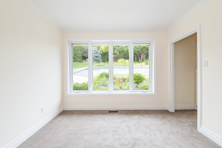 Empty room with large window looking on summer backyard and residential pool photo