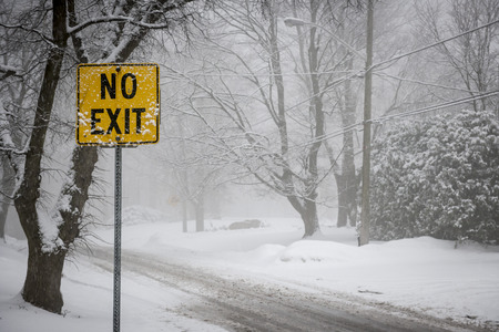 Stormy winter road and trees covered in snow with Yellow No Exit sign photo