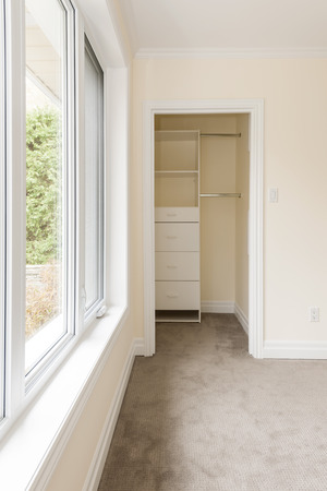 Empty bedroom with large window and closet storage photo