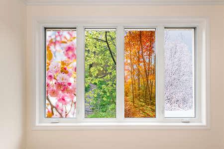 Okno v domácím interiéru s výhledem na čtyři roční období Reklamní fotografie