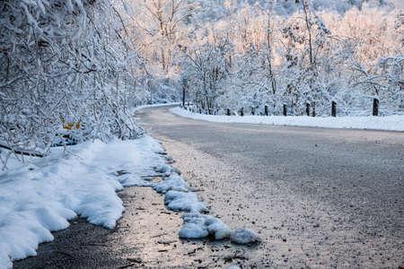 Malerische Winterstraße durch eisigen Wald mit Schnee bedeckt nach Eissturm und Schneefall. Ontario, Kanada. Standard-Bild