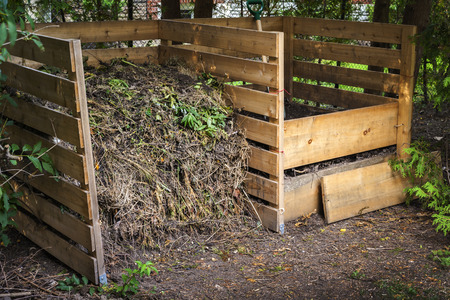 composting: Wooden compost boxes with composted soil and yard waste for garden composting in backyard Stock Photo