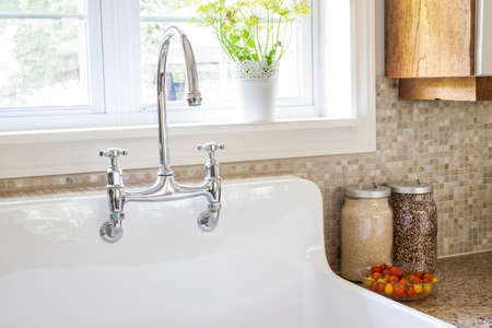 Rustic white porcelain kitchen sink with curved faucet and tile backsplash under large window
