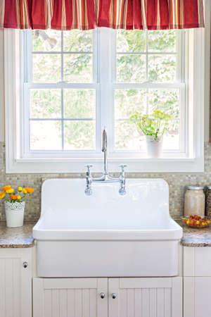 country: Keuken interieur met grote rustieke witte porseleinen spoelbak en granieten stenen aanrecht onder zonnige venster