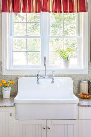 Kitchen interior with large rustic white porcelain sink and granite stone countertop under sunny window photo