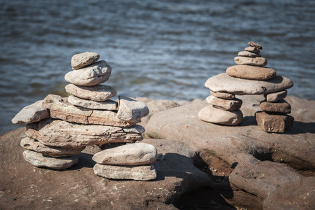cairns: Two small stacked inuksuk or cairns stone landmarks by Atlantic ocean shore. Prince Edward Island, Canada.