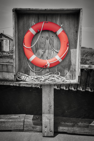 beach buoy: Orange life saver or buoy hanging in wooden box on dock. Prince Edward Island, Canada, selective coloring.