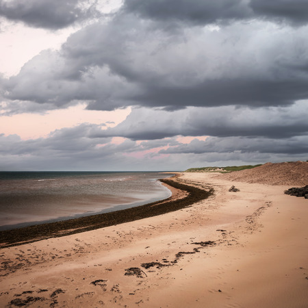 edward: Beach at sunset in Prince Edward Island, Canada with dark cloudy sky, square format