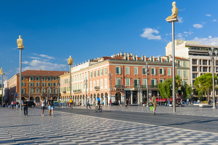 NICE, FRANCE - OCTOBER 2, 2014: Place Massena is the main pedestrian square of the city. Modern statues on tall poles named Conversation in Nice were created by Jaume Plensa and represent the seven continents. Editorial