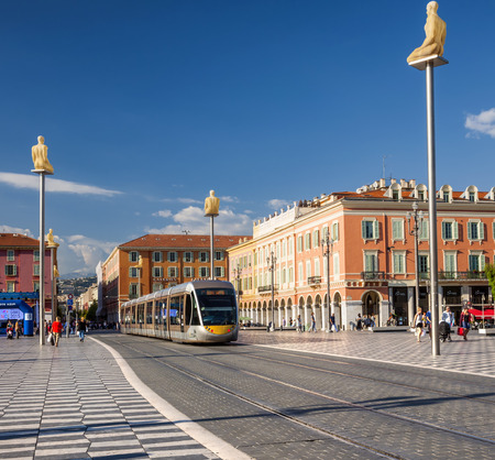 NICE, FRANCE - OCTOBER 2, 2014: Nice tramway entering Place Massena, the main pedestrian square of the city. Artworks surround the line, including sculptures of figures by Jaume Plensa on top of pylons.