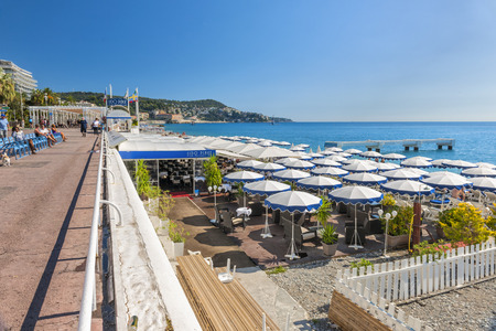 promenade: NICE, FRANCE - OCTOBER 2, 2014: English promenade or Promenade des Anglais runs along the city beach with restaurants, chairs and umbrellas. Editorial