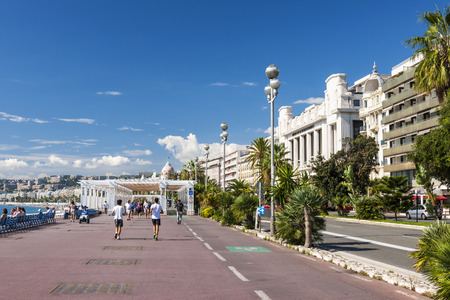 promenade: NICE, FRANCE - OCTOBER 2, 2014: People enjoying sunny weather and view of Mediterranean sea at English promenade (Promenade des Anglais), a great place for walking, jogging, biking or simply relaxing.