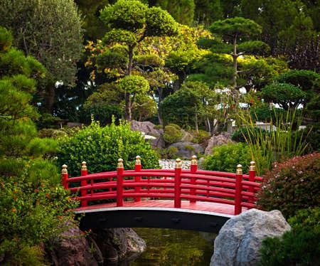 landscaped garden: Red bridge over pond in Japanese garden. Monte Carlo, Monaco. Stock Photo