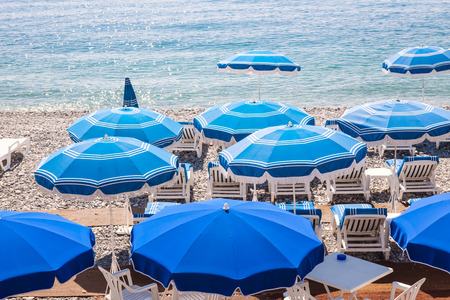 cote d'azur: Blue umbrellas and chairs on pebble beach in Nice, France. Stock Photo