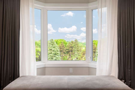 window: Bay window with drapes, curtains and view of trees under summer sky