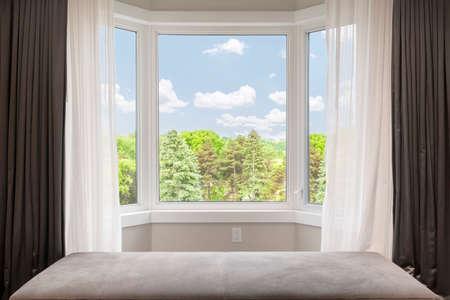 cortinas: Ventana de la bahía con cortinas, cortinas y vista de los árboles bajo el cielo de verano