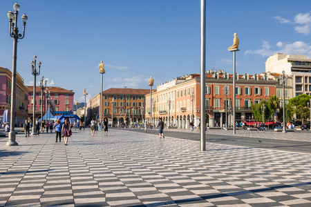 NICE, FRANCE - OCTOBER 2, 2014: People walking on Place Massena, main pedestrian square of the city. Modern statues on tall poles named Conversation in Nice were created by Jaume Plensa and represent the seven continents.