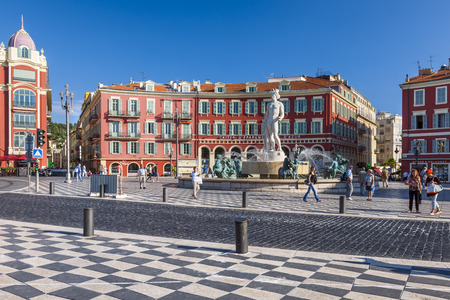 fontaine: NICE, FRANCE - OCTOBER 2, 2014: View of Place Massena with Fountain of the Sun (Fontaine du Soleil) surrounded by red buildings of italian architecture.