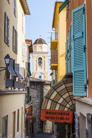 quaint: VILLEFRANCHE-SUR-MER, FRANCE - OCTOBER 4, 2014: Narrow street leading to Eglise Saint-Michel (Saint Michaels Church) is framed by colourful buildings and quaint shops.