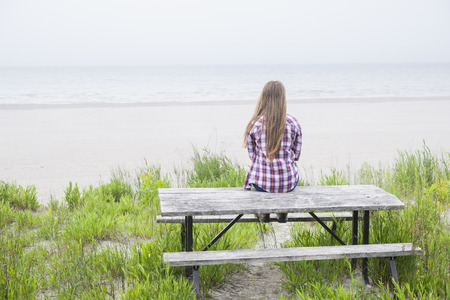 facing: Rear view of young girl with long blond hair sitting on old beach picnic table facing ocean wearing plaid shirt Stock Photo