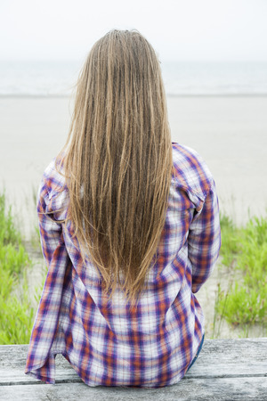 facing: Back view of young woman with long blond hair sitting on misty beach facing ocean wearing plaid shirt