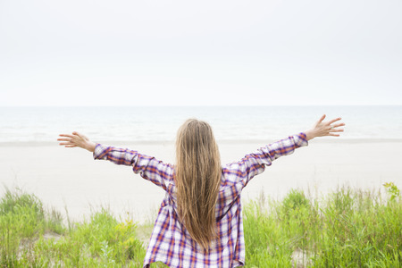 woman from behind: Back view of young woman with long blond hair and outstretched arms on empty beach facing ocean wearing plaid shirt