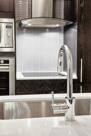 Elegant faucet and sink in island counter of modern kitchen photo