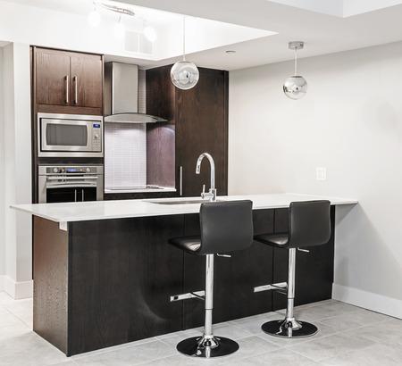 interior designer: Modern luxury kitchen interior with dark wood cabinets, island counter, bar stools and stainless steel appliances Stock Photo
