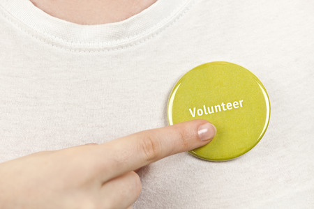 get help: Closeup on female hand pointing to green volunteer button Stock Photo