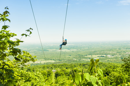 treetop: Young woman zip-lining with aerial countryside view at Blue Mountain, Ontario, Canada.