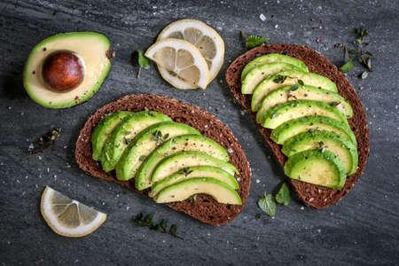 Avocado-Sandwich auf Schwarzbrot mit frisch geschnittenem Avocados von oben gemacht