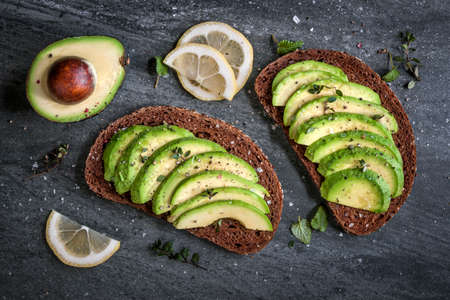 sandwich: Avocado sandwich on dark rye bread made with fresh sliced avocados from above