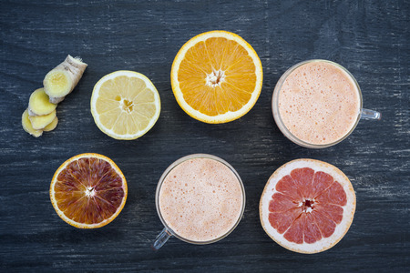 detoxing: Fresh citrus and ginger smoothies with fruit slices on rustic wooden background, view from above Stock Photo