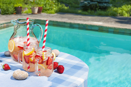 Ice cold homemade strawberry lemonade in jug and glasses with paper straws on outdoor summer pool side table plus copy space