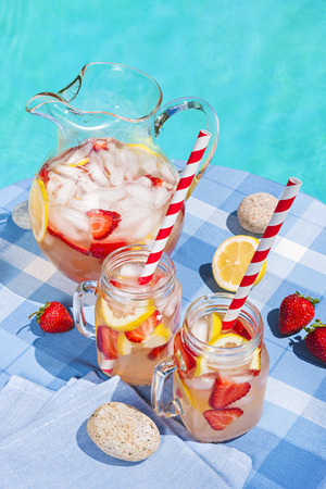 side table: Ice cold homemade strawberry lemonade in jug and glasses with paper straws on outdoor summer pool side table Stock Photo