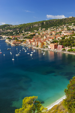 cote d'azur: Aerial view of picturesque French Riviera mediterranean coast with medieval town VillefranchesurMer sandy beach and leisure boats anchored in harbor.