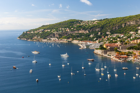 nice  france: Coastal aerial view of Cap de Nice and medieval town VillefranchesurMer on scenic French Riviera with leisure boats anchored in Mediterranean sea harbor