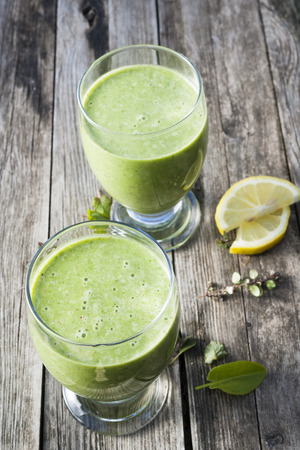 detoxing: Green vegetable smoothies in two glasses on rustic wooden background, view from above