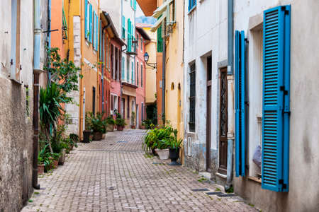 and south: Cobblestone street with colourful buildings and potted plants in old medieval town Villefranche-sur-Mer on French Riviera, France.