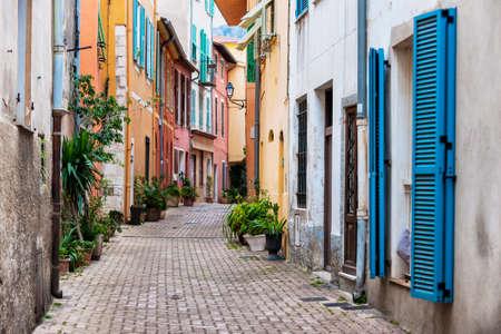 Kopfsteinpflaster-Straße mit bunten Gebäuden und Topfpflanzen im alten mittelalterlichen Stadt Villefranche-sur-Mer auf Französisch Riviera, Frankreich.