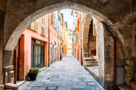 old town: Narrow cobblestone street with colorful buildings viewed though stone arch in medieval town Villefranche-sur-Mer on French Riviera, France. Stock Photo