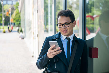 asian business man: Young asian business man looking at mobile phone outside on city street with copy space Stock Photo